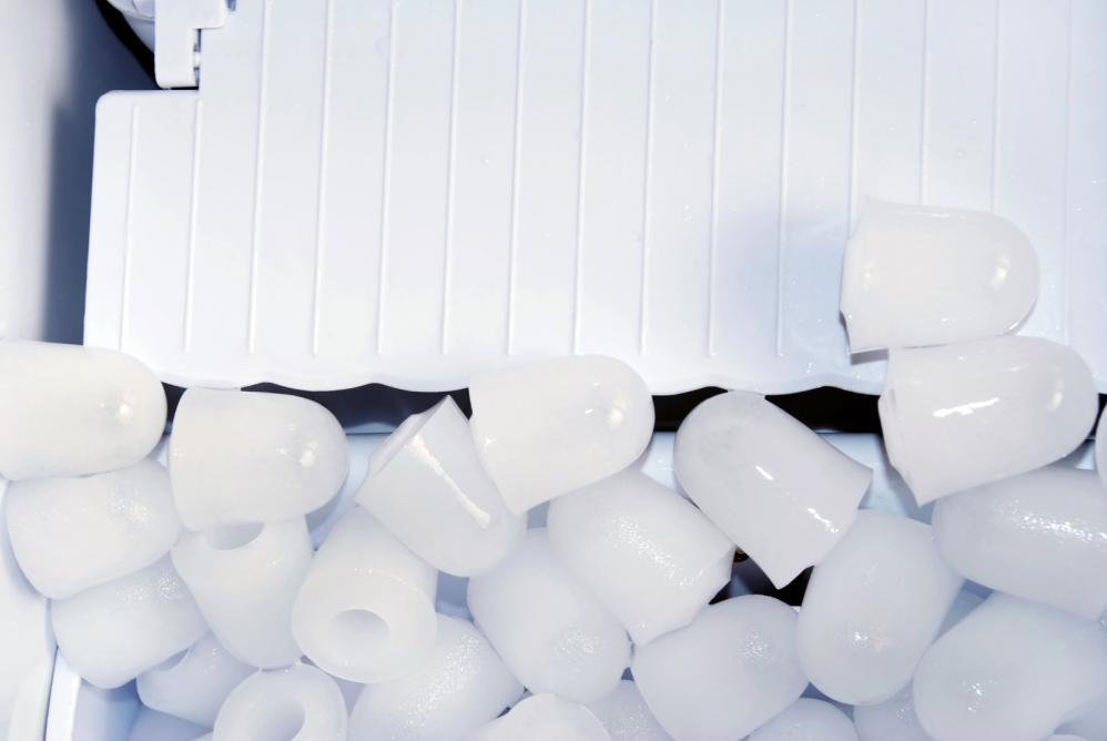Pieces of ice over white plastic in an ice maker
